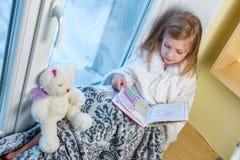 一个逗人喜爱的婴孩在屋子里坐在窗口在冬天并且读书 免版税库存图片
