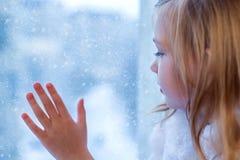 一个逗人喜爱的婴孩在屋子里坐在窗口在冬天 免版税库存图片