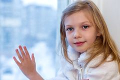 一个逗人喜爱的婴孩在屋子里坐在窗口在冬天 图库摄影