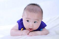 一个逗人喜爱的婴孩在蓝色和说谎穿戴了在床上 库存图片