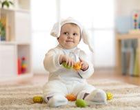 一个逗人喜爱的婴孩的画象在复活节兔子服装在手上穿戴了用鸡蛋 库存照片
