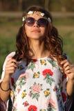 一个逗人喜爱的嬉皮女孩的画象太阳镜的举行手头发技巧户外 免版税图库摄影