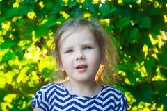 一个逗人喜爱的孩子的画象,女孩是在绿色葡萄叶子背景的面孔  免版税库存照片