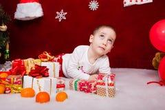 一个逗人喜爱的孩子说谎与礼物 图库摄影