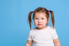 一个逗人喜爱的小女孩在与猪尾巴的蓝色背景微笑着幸福或童年概念的 图库摄影