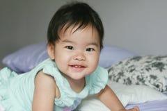 一个逗人喜爱的小女孩在床上爬行 免版税库存照片
