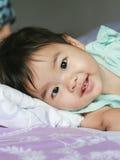一个逗人喜爱的小女孩在床上爬行 库存图片