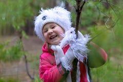 一个逗人喜爱的小女孩在秋天时间的一个杉木森林里 免版税图库摄影