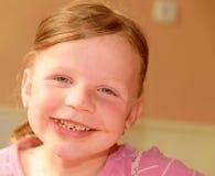 一个逗人喜爱的小女孩微笑 有巧克力奶油的一个小女孩在面孔弄脏 一个小女孩在厨房里坐 免版税库存照片