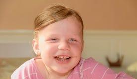 一个逗人喜爱的小女孩微笑 有巧克力奶油的一个小女孩在面孔弄脏 一个小女孩在厨房里坐 免版税库存图片