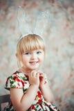 一个逗人喜爱的小女孩的乐趣画象有兔宝宝耳朵的 免版税库存照片