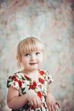 一个逗人喜爱的小女孩的乐趣画象有兔宝宝耳朵的 免版税图库摄影