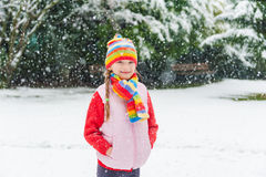 一个逗人喜爱的小女孩的冬天画象在降雪下的 库存图片