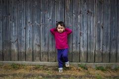 一个逗人喜爱的小女孩的夏天画象由篱芭的 免版税库存照片
