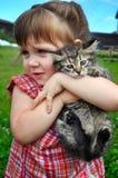 一个逗人喜爱的小女孩的室外画象有小小猫的,使用与在自然本底的猫的女孩 库存图片