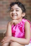 一个逗人喜爱的小女孩的微笑的画象 免版税库存图片