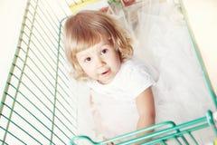 一个逗人喜爱的小女孩的画象一件白色礼服的在有购物的一辆台车坐白色背景 免版税库存照片