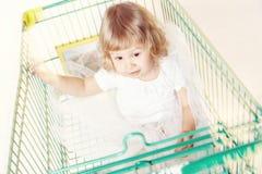 一个逗人喜爱的小女孩的画象一件白色礼服的在有购物的一辆台车坐白色背景 免版税库存图片