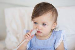 一个逗人喜爱的小女孩的画象一件蓝色礼服的在手上采取一台鼻吸气器 库存照片