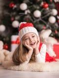 一个逗人喜爱的小女孩的画象圣诞树背景的 库存图片