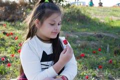 一个逗人喜爱的小女孩的画象在绿色自然背景的晴朗的夏日 夏天喜悦-可爱的女孩吹的蒲公英 免版税库存照片
