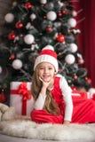 一个逗人喜爱的小女孩的画象圣诞树背景的 库存照片
