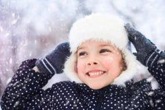 一个逗人喜爱的小女孩的画象在多雪的公园 免版税库存照片