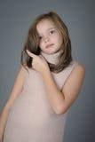 一个逗人喜爱的小女孩的画象推挤她的从她的面孔的头发 库存照片