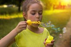 一个逗人喜爱的小女孩的画象有肥皂泡的在一个晴天 图库摄影