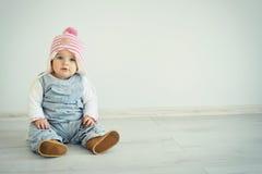 一个逗人喜爱的小女孩调查照相机和戴桃红色被编织的帽子 蓝眼睛孩子 图库摄影