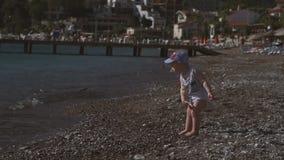 一个逗人喜爱的小孩在海滨站立,投掷小卵石入水,慢动作 股票视频