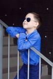 一个逗人喜爱的小男孩在一件蓝色衬衣,长裤打扮并且唱歌 免版税库存照片
