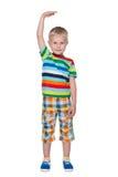 一个逗人喜爱的小男孩显示他怎么是高的 图库摄影
