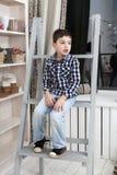 一个逗人喜爱的小男孩的纵向坐楼梯 免版税库存照片