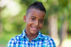 一个逗人喜爱的少年黑人男孩的室外画象-非洲人民 图库摄影