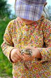一个逗人喜爱的幼儿女孩在手和笑上的拿着一只青蛙蟾蜍 免版税图库摄影
