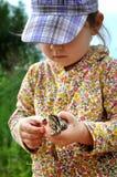 一个逗人喜爱的幼儿女孩在手和笑上的拿着一只青蛙蟾蜍 库存图片