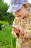 一个逗人喜爱的幼儿女孩在手和笑上的拿着一只青蛙蟾蜍 免版税库存照片