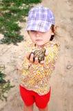 一个逗人喜爱的幼儿女孩在手和笑上的拿着一只青蛙蟾蜍 图库摄影