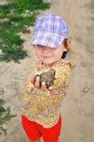 一个逗人喜爱的幼儿女孩在手和笑上的拿着一只青蛙蟾蜍 库存照片