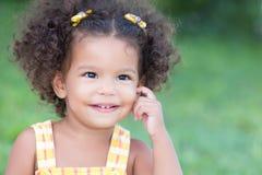 一个逗人喜爱的拉丁女孩的画象有散开的绿色背景 免版税库存照片
