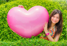 一个逗人喜爱的泰国女孩在绿色叶子bac中拥抱巨型桃红色心脏 库存图片