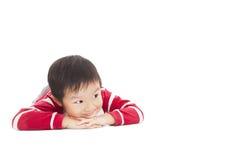 一个逗人喜爱的男孩在地板上认为 库存照片