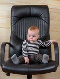 一个逗人喜爱的男孩的乐趣画象办公室椅子的 库存照片
