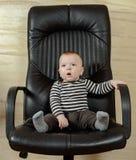 一个逗人喜爱的男孩的乐趣画象办公室椅子的 图库摄影