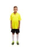 一个逗人喜爱的男孩的充分的高度在白色背景和白色膝盖袜子的隔绝的一只黄色T恤杉、黑短裤 库存图片