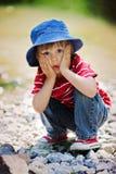 一个逗人喜爱的男孩的画象有夏天帽子的在河的边缘 免版税库存图片