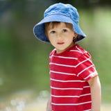 一个逗人喜爱的男孩的画象有夏天帽子的在河的边缘 免版税库存照片