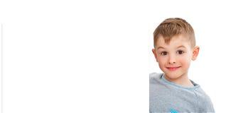 一个逗人喜爱的男孩的画象,偷看从横幅的后面 库存图片