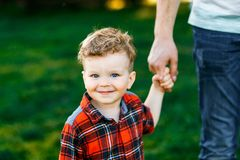 一个逗人喜爱的男孩获得乐趣外面在国家在夏天在日落 使用用黄色蒲公英的男孩在庭院里 免版税图库摄影